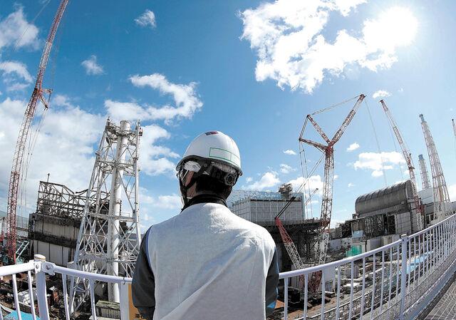 東京電力福島第1原発構内の高台から見える1~4号機と、案内役の東電担当者